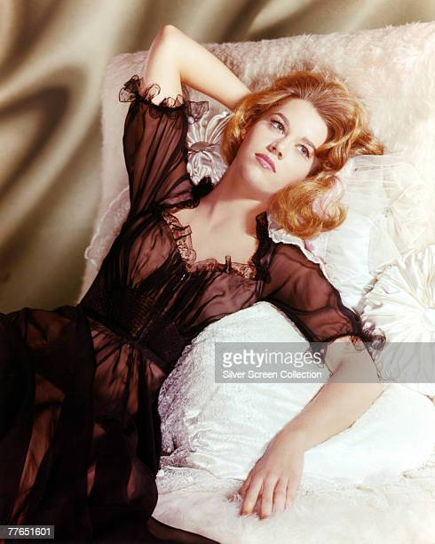 American actress Jane Fonda reclines on satin pillows wearing a diaphanous black negligee circa 1965