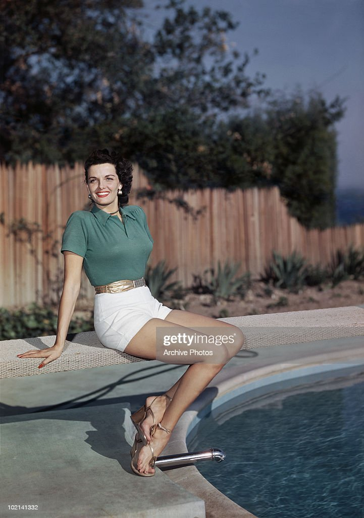 American actress Jane Russell sitting by a pool, circa 1955.