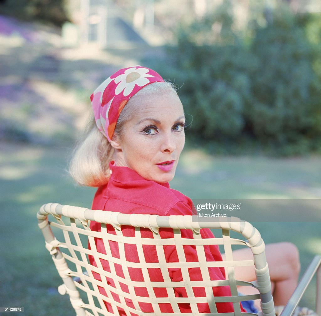 American actress Janet Leigh (1927 - 2004) looks over her shoulder as she sits in a lawn chair and wears a red floral print headscarf, late 1960s.