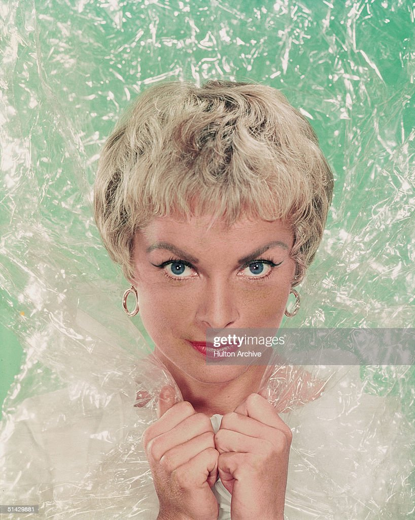 American actress Janet Leigh (1927 - 2004) pokes her head through some sort of transparent plastic material in front of an aqua green background, 1960s.