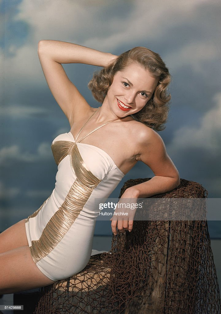 American actress Janet Leigh (1927 - 2004) sits and poses on a fake pier in a white and gold bathing suit, late 1940s.