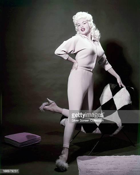 American actress Jayne Mansfield kneeling on a diamondpatterned chair circa 1955