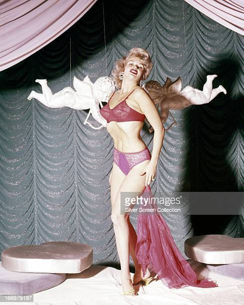 American actress Jayne Mansfield posing in her underwear in front of two suspended cupids circa 1955
