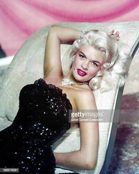 American actress Jayne Mansfield reclining on a chaise longue in a strapless sequined gown and diamond jewelry circa 1955