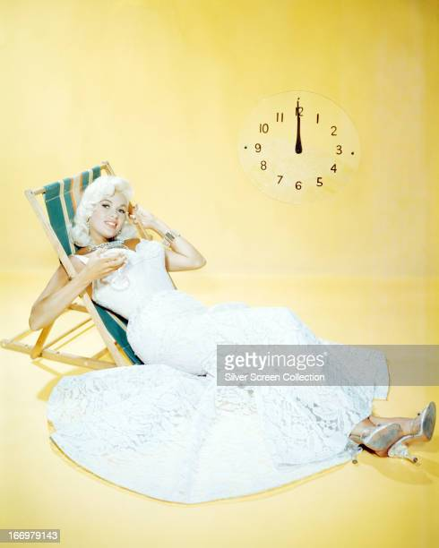 American actress Jayne Mansfield sitting in a deckchair near a large clock and holding a cocktail glass circa 1955