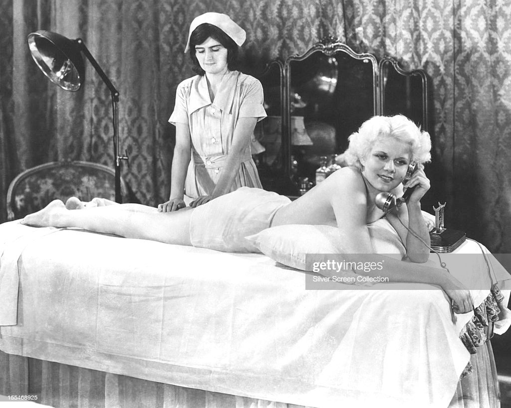 American actress <a gi-track='captionPersonalityLinkClicked' href=/galleries/search?phrase=Jean+Harlow&family=editorial&specificpeople=70012 ng-click='$event.stopPropagation()'>Jean Harlow</a> (1911 - 1937), as Ann Schuyler, makes a phone call, while being massaged in a publicity still for 'Platinum Blonde', directed by Frank Capra, 1931.