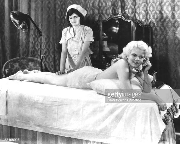 American actress Jean Harlow as Ann Schuyler makes a phone call while being massaged in a publicity still for 'Platinum Blonde' directed by Frank...