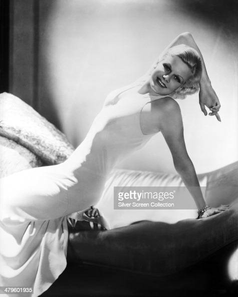 American actress Jean Harlow posing on a chaise longue in a white sleeveless dress circa 1932