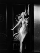 American actress Jean Harlow presses her body to a Romanstyle wall panel