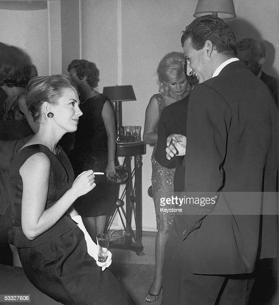 American actress Jean Seberg talking to Italian count Franco Macinelli Scotto who is married to actress Elsa Martinelli at the opening of a new...