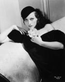 American actress Joan Crawford reclining on a chaise longue holding a flower in a promotional picture for her latest film 'Possessed' Costumes by...