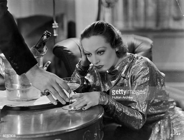 American actress Joan Crawford sits with her head in her hand as a man reaches to take her champagne glass in a still from director Edmund Goulding's...