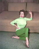 American actress Joan Crawford smoking a cigarette as she sits on the floor next to a sofa circa 1955