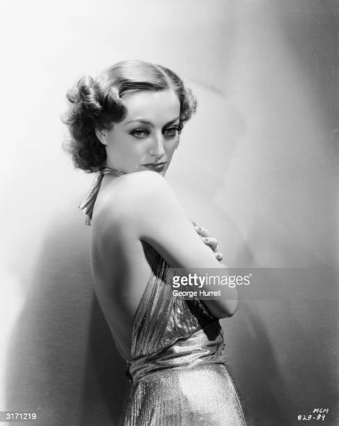 American actress Joan Crawford wearing a backless dress for a publicity picture for her latest film 'No More Ladies'