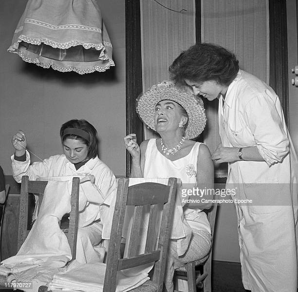 American actress Joan Crawford wearing a hat with veil a necklace earrings and a brooch sitting on a chair in a tailor shop sewing Venice 1970