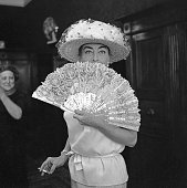 American actress Joan Crawford wearing a hat with veil and smoking a cigarette portrayed while hiding behind a lace fan Venice 1970