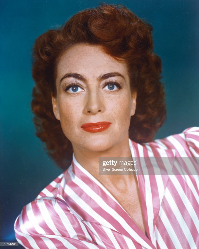 American actress Joan Crawford wearing a pink and white striped blouse circa 1945