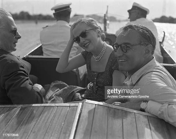American actress Joan Fontaine wearing a fancy dress a pearl necklace and sunglasses sitting on a water taxi with two men Torcello island ahead...