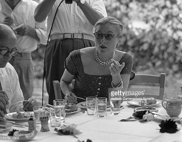 American actress Joan Fontaine wearing a fancy dress a pearl necklace and sunglasses sitting at a restaurant table outdoor in Torcello island Venice...