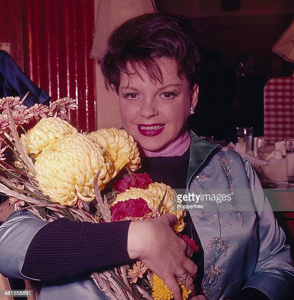 1968 American actress Judy Garland posed with a bouquet of flowers backstage in 1968