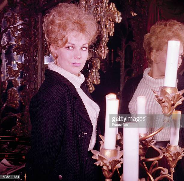 American actress Kim Novak pictured standing next to a mirror in London in 1963