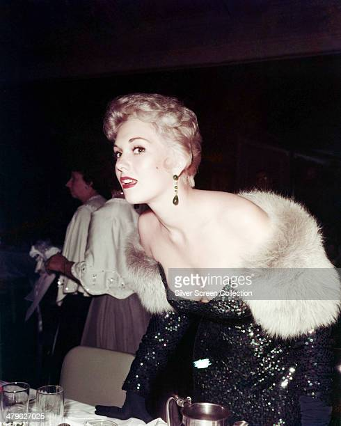 American actress Kim Novak wearing a sequinned offtheshoulder dress at a formal function circa 1955