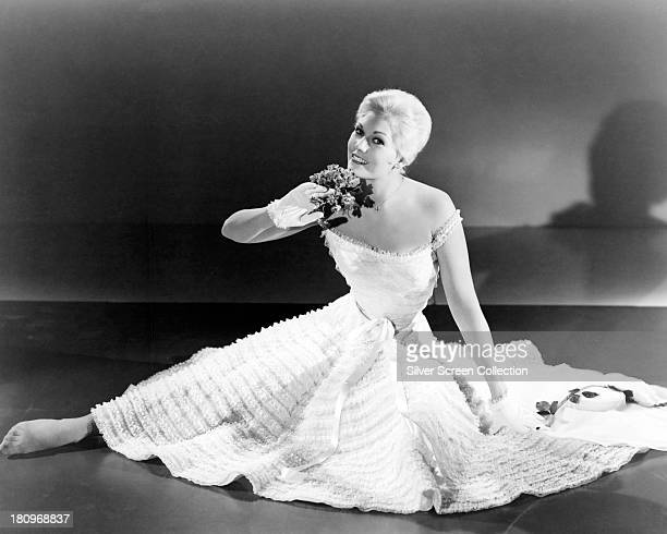 American actress Kim Novak wearing a white fulllength frilled day dress and matching gloves circa 1955