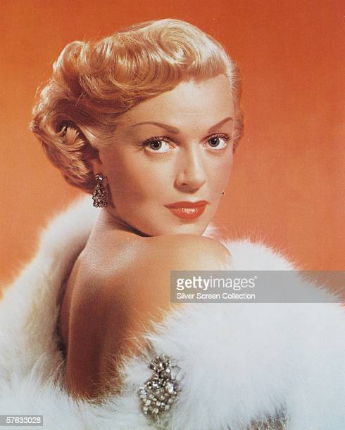 American actress Lana Turner wearing a white fur stole with a jewelled brooch circa 1950