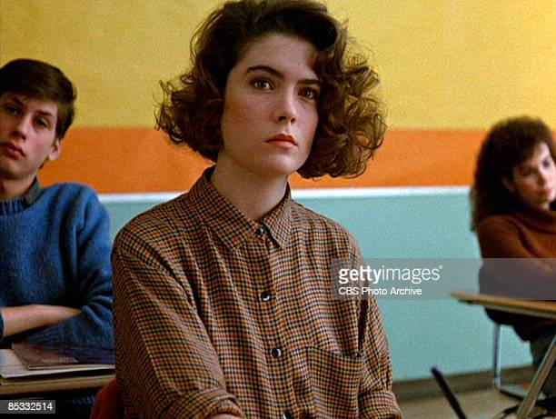 American actress Lara Flynn Boyle sits as a desk in a classroom set in a scene from the pilot episode of the television series 'Twin Peaks'...