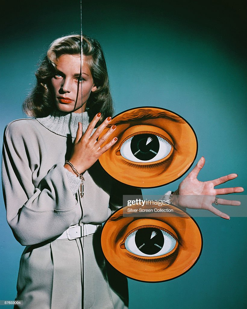 American actress Lauren Bacall poses behind a pane of glass decorated with two giant eyes circa 1950