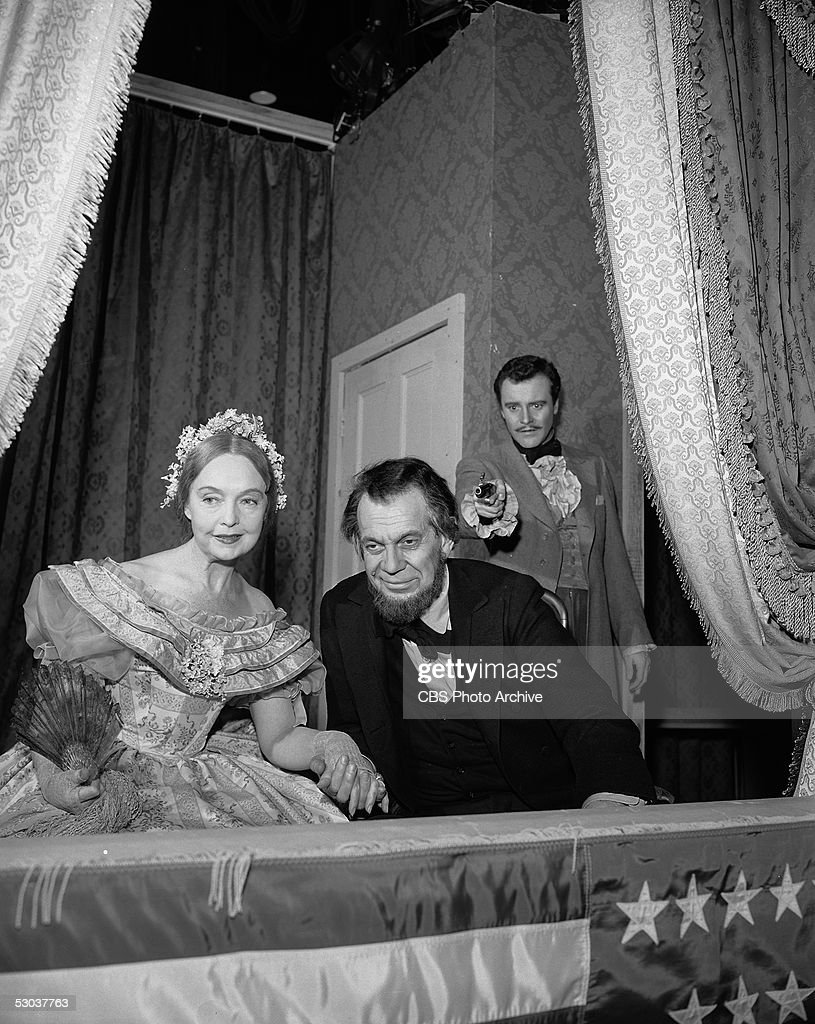 American actress Lillian Gish (1893 - 1993), as Mary Todd Lincoln, holds hands with Canadian actor Raymond Massey (1896 - 1983), as President Abraham Lincoln, as they watch a play from the balcony while American actor Jack Lemmon (1925 - 2001), as John Wilkes Booth, aims a gun at Massey in an episode of the dramatic anthology series 'Ford Star Jubilee' called 'The Day Lincoln Was Shot,' New York, New York, February 11, 1956.