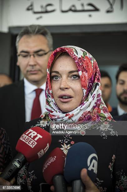 American actress Lindsay Lohan speaks to press members with wearing a headscarf given by a Syrian woman after her visit at a container town where...