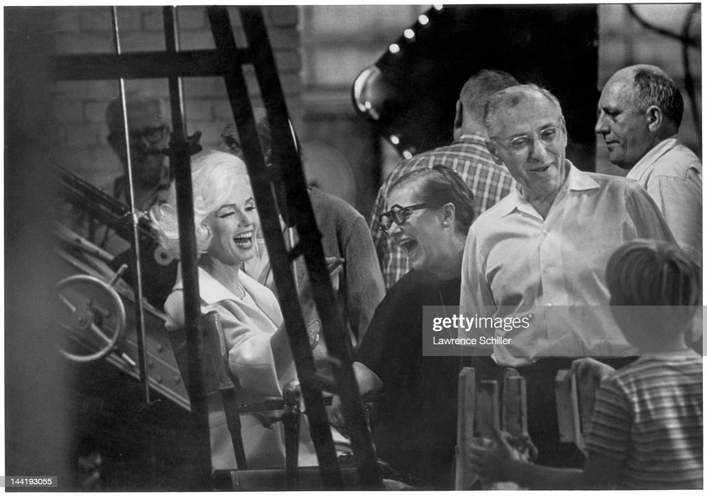 American actress Marilyn Monroe (1926 - 1962) (left) and her dialogue coach Paula Strasberg (1911 - 1966) (center, in round glasses) share a laugh on set during the filming of 'Something's Got to Give' (directed by George Cukor), Los Angeles, California, mid 1962. Film director George Cukor (1899 - 1983) is at right fore.