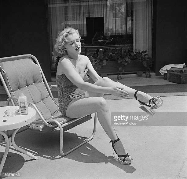 American actress Marilyn Monroe applies Nivea lotion to her legs circa 1951