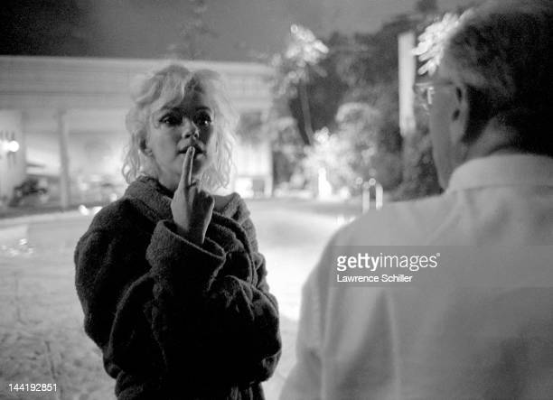 APPLY American actress Marilyn Monroe dressed in a bathrobe talks with film director George Cukor beside a pool during the filming of a scene from...