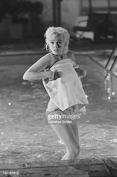 APPLY American actress Marilyn Monroe holds a towel in front of her as she stands topless in a pool during the filming of 'Something's Got to Give'...