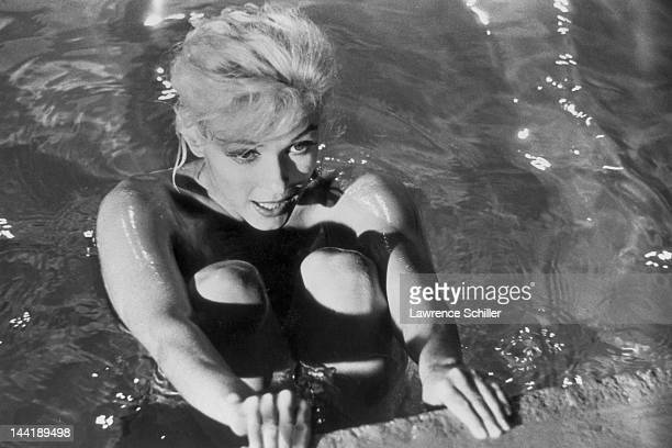 APPLY American actress Marilyn Monroe holds the edge of a pool and lifts her knees to her chest during the filming of 'Something's Got to Give' Los...