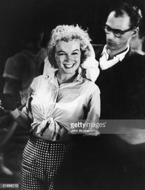 American actress Marilyn Monroe laughs while her husband American playwright Arthur Miller dries her hair after a dance rehearsal for director George...