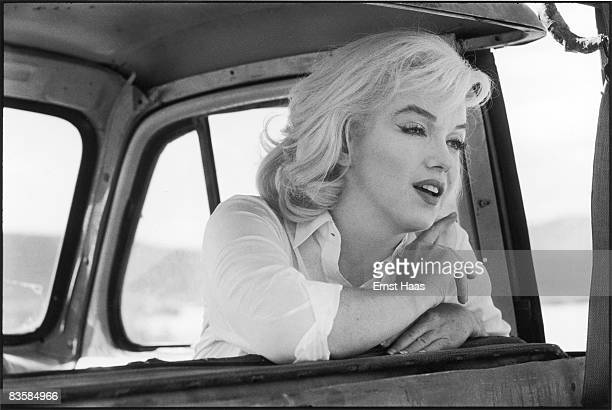 American actress Marilyn Monroe leans over the back of the front seat of a car on the set of 'The Misfits' directed by John Huston Nevada 1960