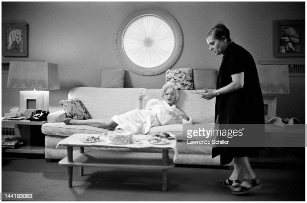 American actress Marilyn Monroe lies on a couch as she and her dialogue coach Paula Strasberg share a meal in Monroe's dressing room during the...