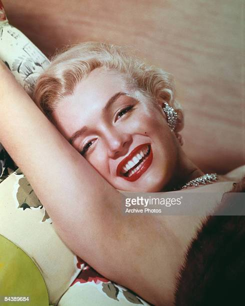 American actress Marilyn Monroe lies smiling on a couch circa 1955