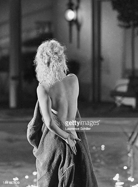 APPLY American actress Marilyn Monroe naked pulls on a blue bathrobe on the deck of a pool during the filming of 'Something's Got to Give' Los...