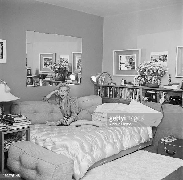 American actress Marilyn Monroe relaxes on a sofa bed circa 1951 The book she is reading is 'The Poetry and Prose of Heinrich Heine'