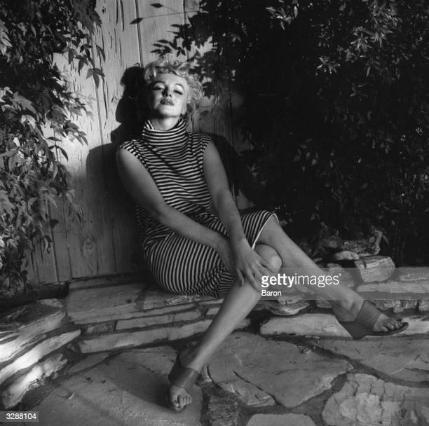 American actress Marilyn Monroe sits in shadow against a garden fence 1954
