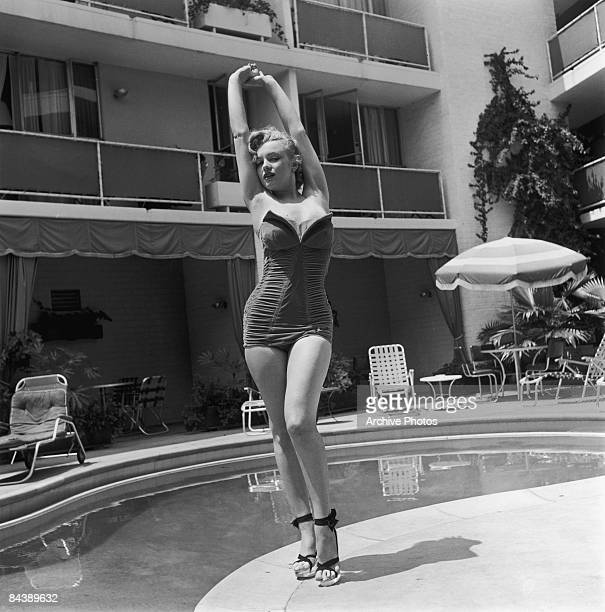American actress Marilyn Monroe stands next to a swimming pool in a strapless swimsuit and high heels circa 1951