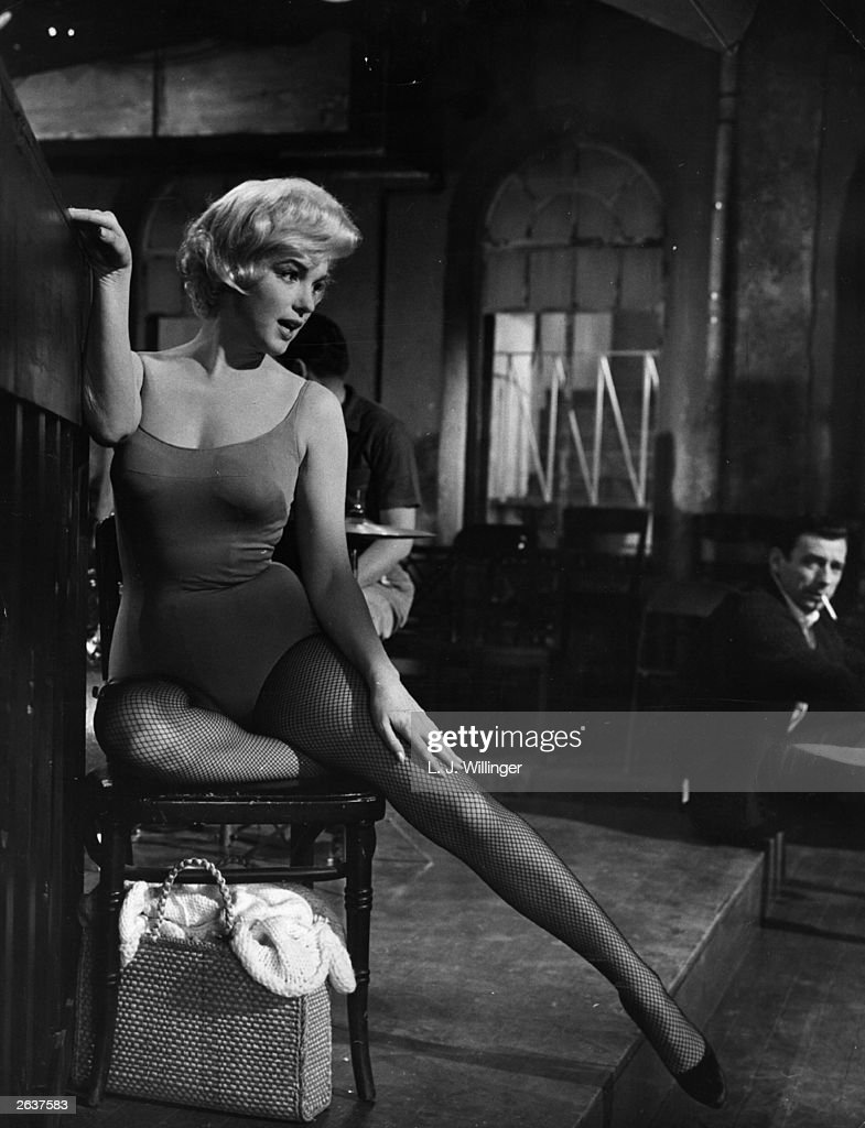 American actress Marilyn Monroe stretches her leg under the watchful eye of Yves Montand on the set of the 20th Century Fox film 'Let's Make Love'...