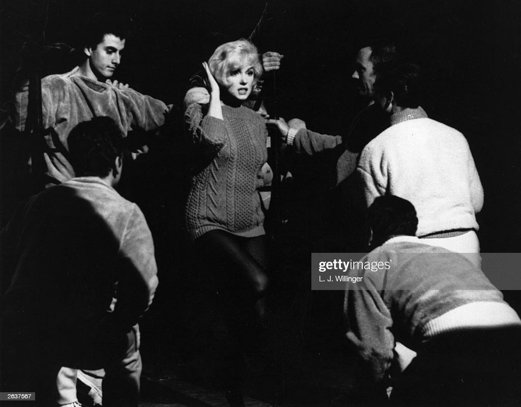 American actress Marilyn Monroe talking to the Jack Cole dancers between takes on the set of the 20th Century Fox film 'Let's Make Love' The film is...