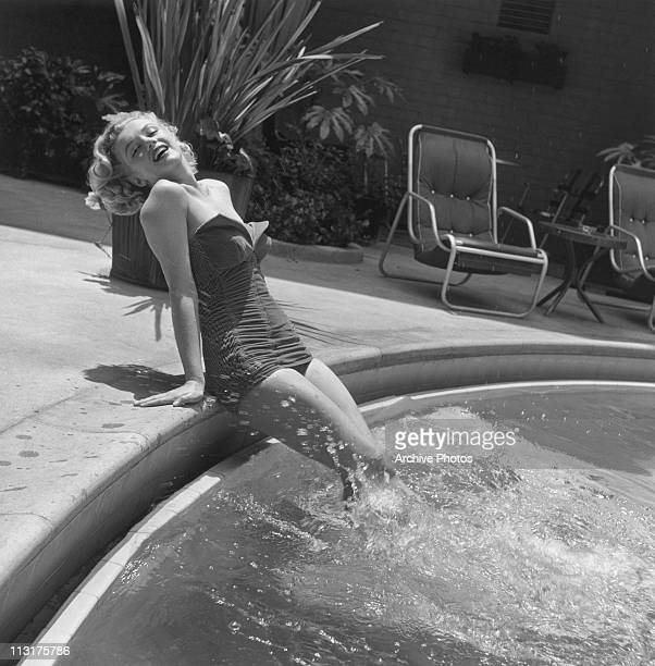 American actress Marilyn Monroe wearing a bathing suit and with her legs in a swimming pool circa 1951