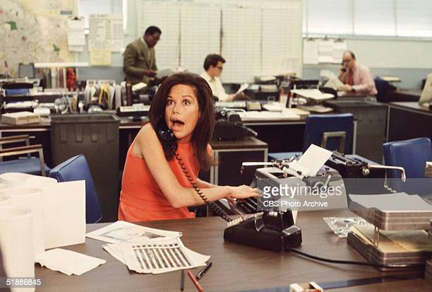 American actress Mary Tyler Moore mouths surprise on the telephone while simultaneously typing as others work in the background in a scene from 'The...