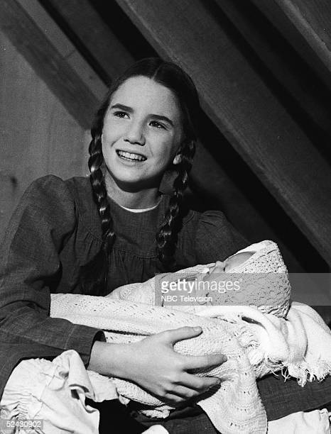 American actress Melissa Gilbert holds a baby doll in a scene from the episode 'Be My Friend' of the television series 'Little House on the Prairie'...
